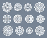 Mandalas set. White snowflakes isolated on gray