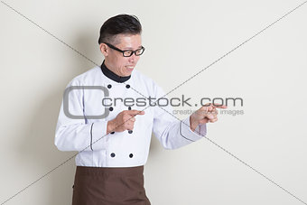 Mature Asian Chinese chef pointing