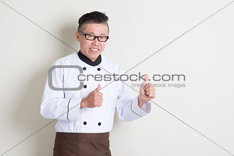 Mature Asian chef thumbs up