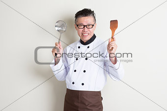 Mature Asian Chinese chef with kitchen tools