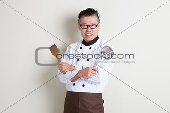 Mature Asian Chinese chef holding kitchen tools