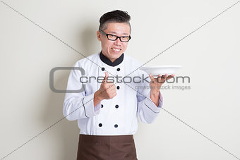 Mature Asian Chinese chef presenting dish and thumb up