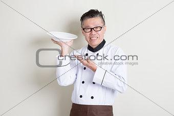 Mature Asian chef presenting dish