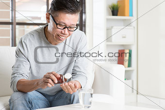 Asian man eating supplement
