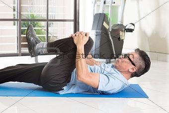 Mature Asian man exercise at gym