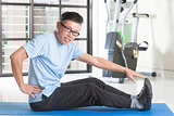 Mature Asian man exercising at gym