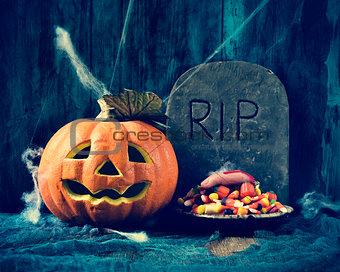 carved pumpkin, gravestone and Halloween candies