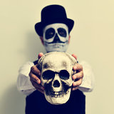 man with calaveras makeup holding a skull