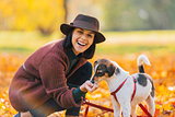 Portrait of young woman feeding dog in autumn park