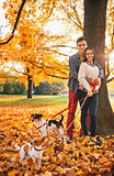 Portrait of couple with two little dogs on the walk in park