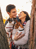 Happy young couple holding dogs in park and smiling