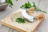Fresh parsley on a board with mezzaluna