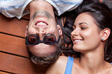 Happy young couple lying on a wooden floor