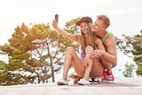 Happy couple with sitting on skateboard and taking a selfie