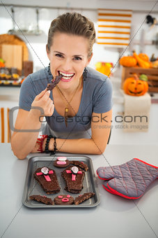 Housewife eating freshly homemade Halloween biscuits in kitchen