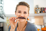 Funny modern housewife making mustache with Halloween biscuit