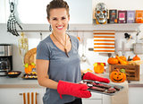 Smiling housewife holding tray with baked Halloween biscuits