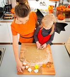 Girl in bat costume with mother making Halloween biscuits
