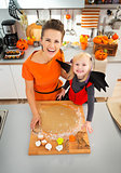 Mother with daughter in bat costume making Halloween cookies