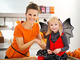 Girl in bat costume with mother holding Halloween cookies