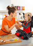 Halloween dressed girl with mother holding uncooked biscuits