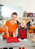 Mother with halloween dressed girl wearing oven mitts in kitchen