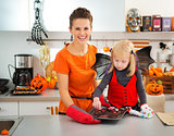 Girl with mother holding tray with Halloween biscuits in kitchen