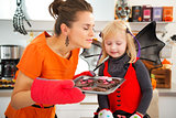 Girl with mother enjoying the aroma of Halloween biscuits