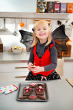 Funny girl in bat costume holding freshly Halloween cookies