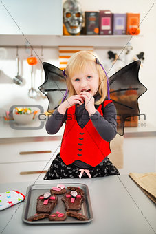 Blond girl in bat costume eating Halloween biscuits in kitchen
