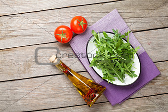 Arugula salad, tomatoes and olive oil bottle
