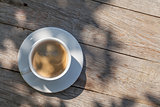 Coffee cup on sunny garden table