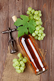 Bunch of grapes, white wine bottle and corkscrew