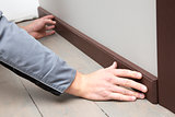 installation of a brown wooden baseboard at the bottom of the wa