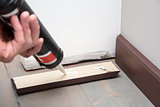 home improvement, pushing glue on the wooden baseboard