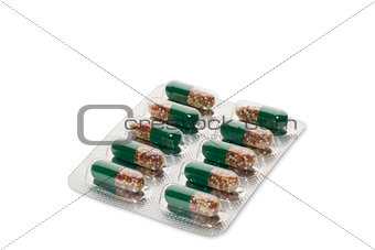 Green pills in a blister pack on white background