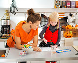 Halloween dressed girl and mother drawing Jack-O-Lantern