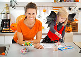 Mother with girl in halloween costume drawing Jack-O-Lantern