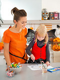 Mother with halloween dressed blond girl drawing Jack-O-Lantern