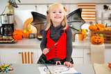 Girl in halloween bat costume drawing Jack-O-Lantern on paper