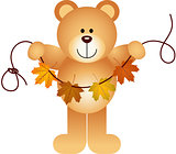 Teddy bear holding a garland of fall leaves