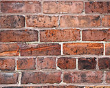 Close up of textured wall of red bricks and cement