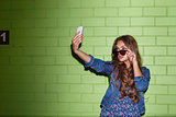 beautiful long-haired woman with a smartphone near a green brick
