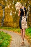 slim blonde walks alone in the park