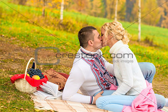 young couple in love kissing on a picnic on a blanket
