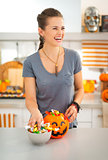Laughing woman preparing halloween trick or treat candy for kids