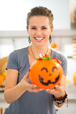 Woman holding halloween bucket full of trick or treat candy