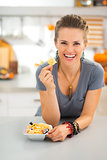 Happy young woman in kitchen showing halloween boo chips treats