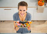 Woman showing dish with trick or treat candy for halloween party