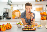 Smiling woman eating trick or treat halloween candy